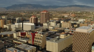 DX0002_127_032 - 5.7K stock footage aerial video orbit and fly away from Albuquerque Plaza high-rise towering over city buildings, Downtown Albuquerque, New Mexico