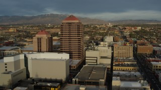 DX0002_127_042 - 5.7K stock footage aerial video approach and then orbit office high-rise at the center of city buildings, Downtown Albuquerque, New Mexico