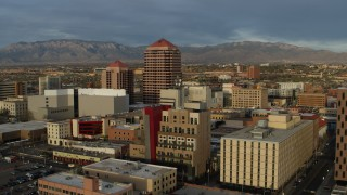 DX0002_127_044 - 5.7K stock footage aerial video circling office high-rise at the center of city buildings, Downtown Albuquerque, New Mexico