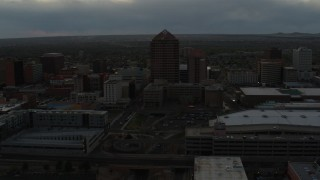 DX0002_128_003 - 5.7K stock footage aerial video of orbiting office high-rise beside hotel at sunset, Downtown Albuquerque, New Mexico