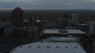 DX0002_128_008 - 5.7K stock footage aerial video orbiting the office high-rise, hotel, Kiva Auditorium at sunset, Downtown Albuquerque, New Mexico