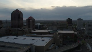 DX0002_128_010 - 5.7K stock footage aerial video reverse view of office tower, hotel, Kiva Auditorium, convention center at sunset, Downtown Albuquerque, New Mexico