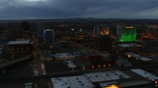 DX0002_128_019 - 5.7K stock footage aerial video approach office buildings near hotel at twilight, Downtown Albuquerque, New Mexico