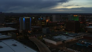 DX0002_128_021 - 5.7K stock footage aerial video orbit and fly away from hotel and office buildings at twilight, Downtown Albuquerque, New Mexico