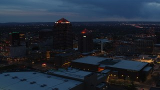 DX0002_128_027 - 5.7K stock footage aerial video ascend with view of office high-rise, hotel and Kiva Auditorium at twilight, Downtown Albuquerque, New Mexico