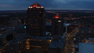DX0002_128_031 - 5.7K stock footage aerial video orbit and fly away from office high-rise and hotel at twilight, Downtown Albuquerque, New Mexico