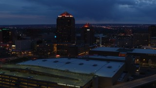 DX0002_128_033 - 5.7K stock footage aerial video orbit office high-rise, hotel, seen from convention center at twilight, Downtown Albuquerque, New Mexico