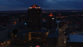 DX0002_128_035 - 5.7K stock footage aerial video fly toward and circle office high-rise beside hotel at twilight, Downtown Albuquerque, New Mexico