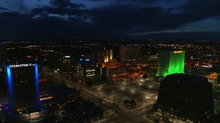 DX0002_128_043 - 5.7K stock footage aerial video orbit and fly away from office buildings at twilight, reveal hotel, Downtown Albuquerque, New Mexico