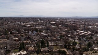 DX0002_129_024 - 5.7K stock footage aerial video ascend and flyby the downtown area and surrounding city of Santa Fe, New Mexico