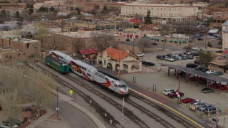 DX0002_130_016 - 5.7K stock footage aerial video orbit passenger train at the station in Santa Fe, New Mexico