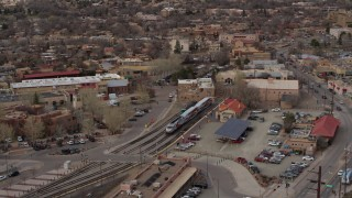DX0002_130_022 - 5.7K stock footage aerial video fly around a passenger train at a station in Santa Fe, New Mexico, tilt to top of the train