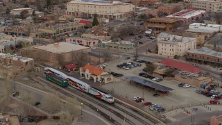 DX0002_130_023 - 5.7K stock footage aerial video approach and tilt to a passenger train at a station in Santa Fe, New Mexico, tilt to top of the train
