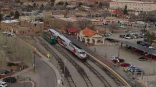 DX0002_130_024 - 5.7K stock footage aerial video descend near a passenger train at a station in Santa Fe, New Mexico