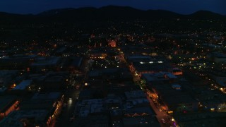 DX0002_132_018 - 5.7K stock footage aerial video ascend by downtown, reveal San Francisco Street leading to cathedral at night, Santa Fe, New Mexico
