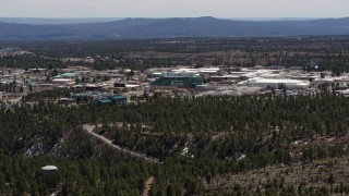 DX0002_133_034 - 5.7K stock footage aerial video of slowly flying away from the Los Alamos National Laboratory, New Mexico