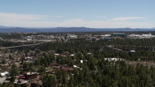 DX0002_134_001 - 5.7K stock footage aerial video ascend from trees, reveal Los Alamos National Laboratory, New Mexico