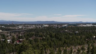 DX0002_134_007 - 5.7K stock footage aerial video rising from behind trees, reveal Los Alamos National Laboratory, New Mexico
