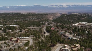 DX0002_134_012 - 5.7K stock footage aerial video road near homes and mesas with a view of mountains in Los Alamos, New Mexico