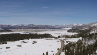 DX0002_134_017 - 5.7K stock footage aerial video of flying by country road in snowy valley with view of mountains, New Mexico