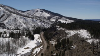 DX0002_134_031 - 5.7K stock footage aerial video reverse view of black car on winding road between snowy mountains and evergreens, New Mexico