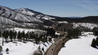 DX0002_134_033 - 5.7K stock footage aerial video flyby winding road by snowy mountains, reveal black cars, New Mexico