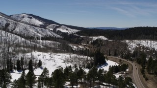 DX0002_134_034 - 5.7K stock footage aerial video passing winding road and four black cars by snowy mountains, New Mexico