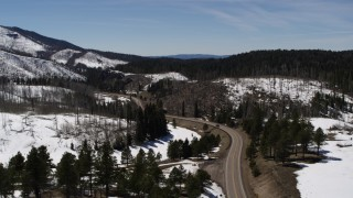 DX0002_134_035 - 5.7K stock footage aerial video flyby black car on winding road by snowy mountains, New Mexico