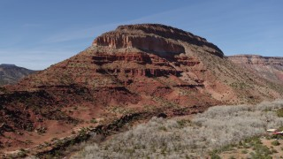 DX0002_135_002 - 5.7K stock footage aerial video orbit and fly away from a butte beside a road, New Mexico