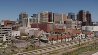 DX0002_136_019 - 5.7K stock footage aerial video approach a train station with city skyline behind it in Downtown Phoenix, Arizona