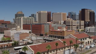 DX0002_136_020 - 5.7K stock footage aerial video of a reverse view of a train station and city skyline of Downtown Phoenix, Arizona