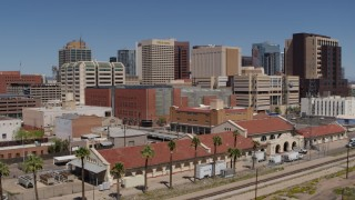 DX0002_136_023 - 5.7K stock footage aerial video of flying away from a train station and the city's skyline, Downtown Phoenix, Arizona