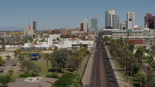 DX0002_137_038 - 5.7K stock footage aerial video flyby palm trees at city park and street leading to tall office buildings in Downtown Phoenix, Arizona