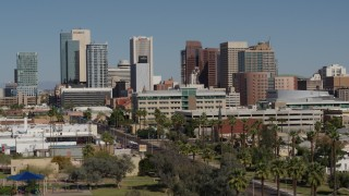 DX0002_137_053 - 5.7K stock footage aerial video of towering office buildings seen from street lined with palm trees in Downtown Phoenix, Arizona
