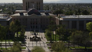 DX0002_137_067 - 5.7K stock footage aerial video approach flags in front of the Arizona State Capitol building in Phoenix, Arizona