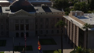 DX0002_137_068 - 5.7K stock footage aerial video fly away from flags in front of the Arizona State Capitol building in Phoenix, Arizona