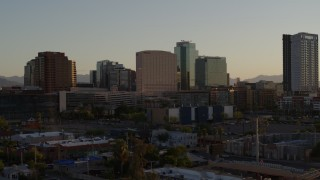 DX0002_138_051 - 5.7K stock footage aerial video of passing a hotel and tall office buildings at sunset in Downtown Phoenix, Arizona