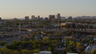 DX0002_138_052 - 5.7K stock footage aerial video of tall office buildings in the distance at sunset in Phoenix, Arizona