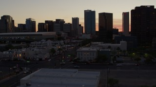DX0002_139_005 - 5.7K stock footage aerial video of passing tall office buildings at sunset, reveal college buildings in Downtown Phoenix, Arizona