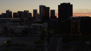DX0002_139_008 - 5.7K stock footage aerial video of tall office high-rises at sunset seen from busy street in Downtown Phoenix, Arizona