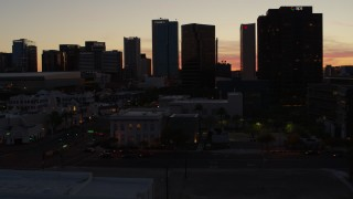DX0002_139_011 - 5.7K stock footage aerial video of approaching tall office high-rises at sunset in Downtown Phoenix, Arizona