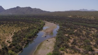 DX0002_141_001 - 5.7K stock footage aerial video of following a shallow river through the desert, fly over horses
