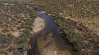 DX0002_141_005 - 5.7K stock footage aerial video fly away from a group of horses beside a shallow desert river