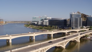 DX0002_142_007 - 5.7K stock footage aerial video black car and truck on bridge near office buildings in Tempe, Arizona