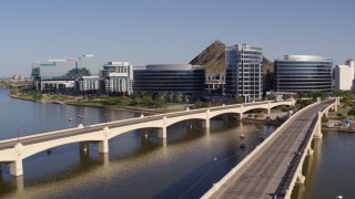 DX0002_142_008 - 5.7K stock footage aerial video fly away from and past bridges leading to waterfront office buildings in Tempe, Arizona