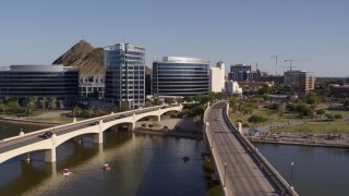 DX0002_142_009 - 5.7K stock footage aerial video orbiting waterfront office buildings beside bridges spanning Tempe Town Lake in Tempe, Arizona