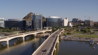DX0002_142_010 - 5.7K stock footage aerial video orbiting waterfront office buildings seen from bridges spanning Tempe Town Lake in Tempe, Arizona
