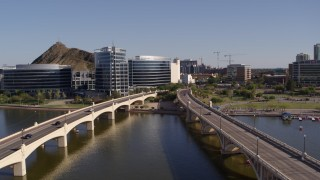 DX0002_142_011 - 5.7K stock footage aerial video fly away from waterfront office buildings and descend between bridges in Tempe, Arizona