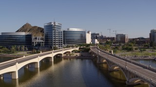 DX0002_142_012 - 5.7K stock footage aerial video ascend and approach waterfront office buildings from bridges in Tempe, Arizona