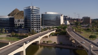 DX0002_142_013 - 5.7K stock footage aerial video fly away from waterfront office buildings, seen from between two bridges in Tempe, Arizona